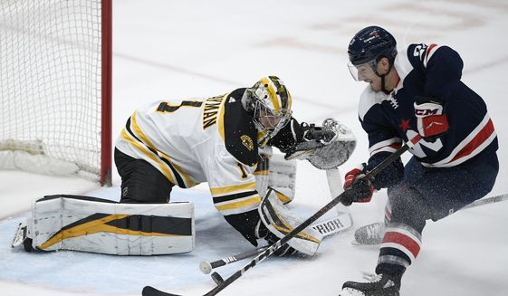 Boston Bruins goaltender Jeremy Swayman (1) defends against Washington Capitals right wing Garnet Hathaway, right, during the first period of an NHL hockey game Thursday, April 8, 2021, in Washington. (AP Photo/Nick Wass)