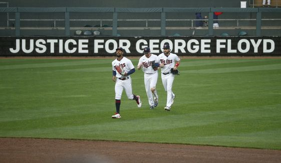 "Minnesota Twins' Byron Buxton, Kyle Garlick, and Jake Cave, left to right, celebrate the 10-2 win over Seattle Mariners in front of a Target Field sign that reads ""Justice for George Floyd"" at a baseball game Thursday, April 8, 2021, in Minneapolis. (AP Photo/Bruce Kluckhohn)"