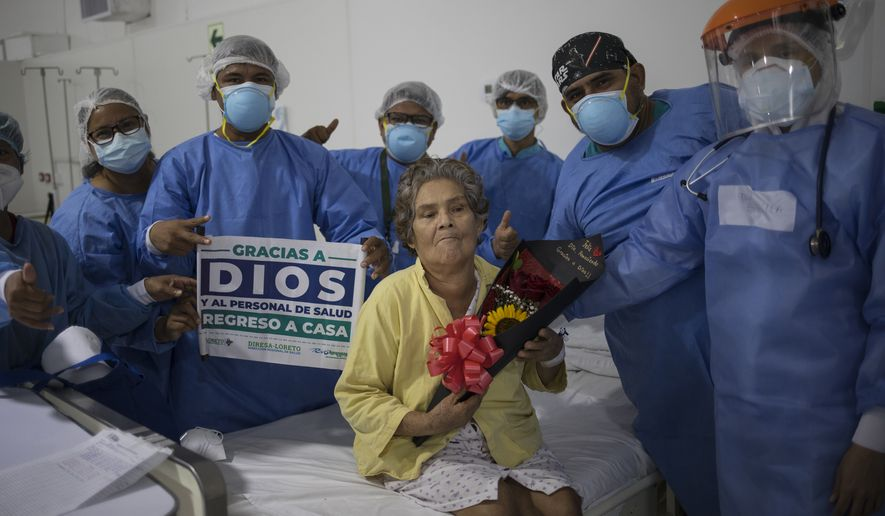 Doctors and nurses pose for a photo with COVID-19 patient Hilda Noriega, 76, to celebrate her recovery, at the Regional Hospital in Iquitos, Peru, Monday, March 22, 2021.(AP Photo/Rodrigo Abd)