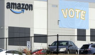 In this Tuesday, March 30, 2021, file photo, a banner encouraging workers to vote in labor balloting is shown at an Amazon warehouse in Bessemer, Ala. (AP Photo/Jay Reeves, File)