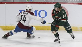 Minnesota Wild's Kirill Kaprizov (97) and Colorado Avalanche's Jacob MacDonald (34) go after the puck during the first period of an NHL hockey game Wednesday, April 7, 2021, in St. Paul, Minn. (AP Photo/Stacy Bengs)