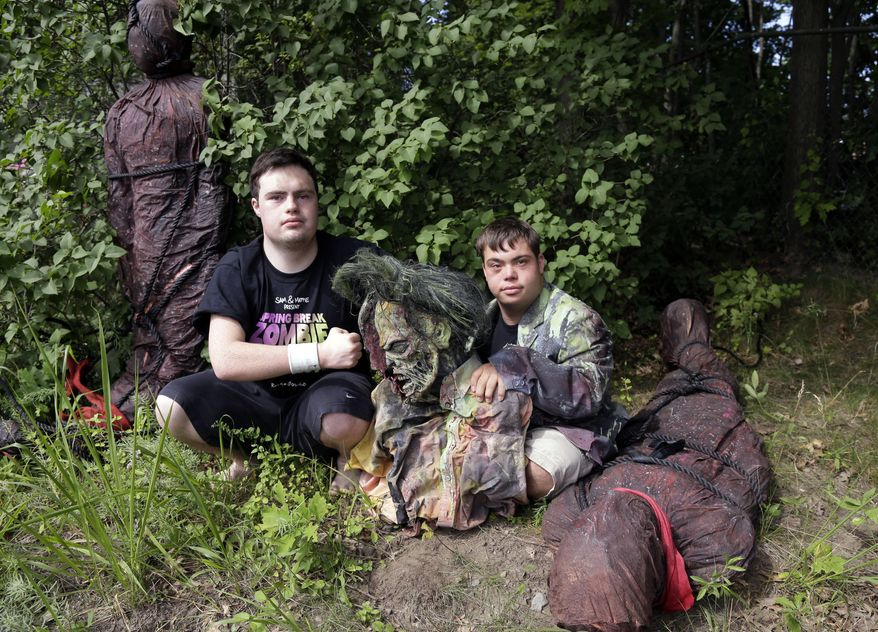 "FILE - In this July 12, 2016, file photo, Sam Suchmann, left, and Mattie Zufelt pose with ghoulish figures at Sam's home in Providence, R.I. The two young men who caused a sensation four years ago when they created their own gory zombie movie are back, this time in a documentary championed by a Hollywood luminary that chronicles their tenacious, years-long effort to see their silver screen dream come to fruition. ""Sam & Mattie Make a Zombie Movie,"" was released Tuesday, April 6, 2021, on Apple TV. (AP Photo/Elise Amendola, File)"