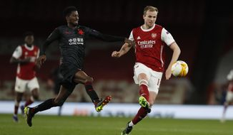 Arsenal's Rob Holding, right, passes the ball as Slavia Prague's Peter Olayinka tries to sop him during the Europa League quarterfinal soccer match between Arsenal and Slavia Prague at Emirates stadium in London, Thursday, April 8, 2021. (AP Photo/Alastair Grant)