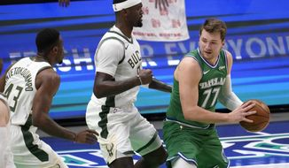 Milwaukee Bucks forward Thanasis Antetokounmpo (43) and center Bobby Portis, center, defend as Dallas Mavericks guard Luka Doncic (77) looks to the basket for a shot in the first half of an NBA basketball game in Dallas, Thursday, April 8, 2021. (AP Photo/Tony Gutierrez)