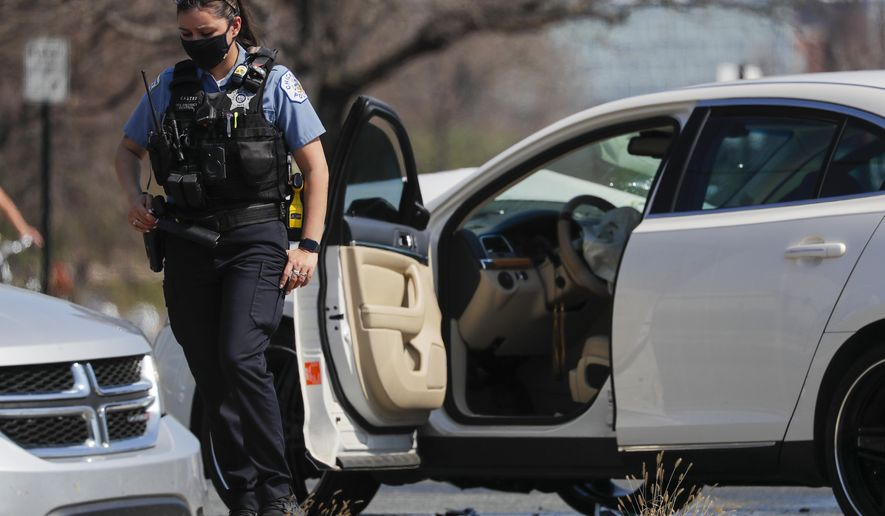 A Chicago police officer stands on the scene of a shooting where a 2-year-old boy was shot in the head while he was traveling inside a car near Grant Park, Tuesday, April 6, 2021. (Jose M. Osorio/Chicago Tribune via AP)