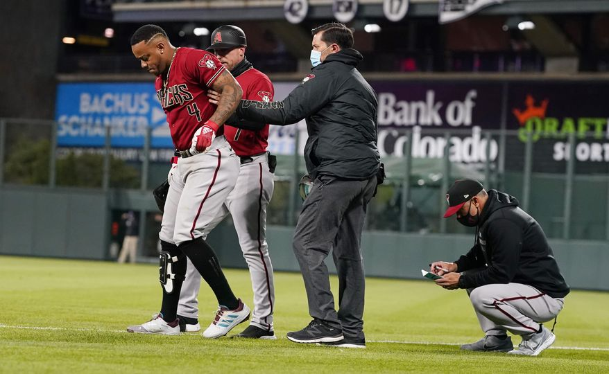 Arizona Diamondbacks' Ketel Marte, left, is helped off the field after injuring his leg while running out a ground ball during the sixth inning of the team's baseball game against the Colorado Rockies on Wednesday, April 7, 2021, in Denver. (AP Photo/David Zalubowski)