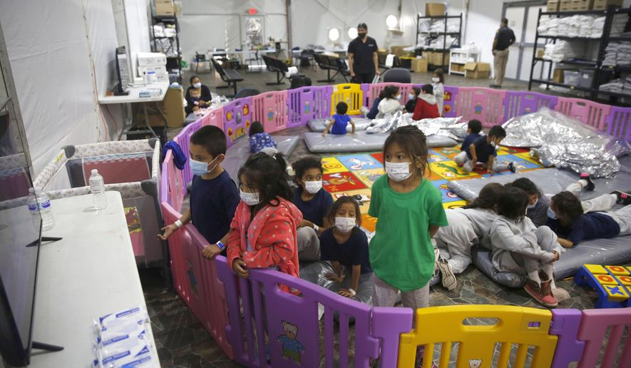 In this March 30, 2021, file photo, young unaccompanied migrants, from ages 3 to 9, watch television inside a playpen at the U.S. Customs and Border Protection facility, the main detention center for unaccompanied children in the Rio Grande Valley, in Donna, Texas. (AP Photo/Dario Lopez-Mills, Pool, File)