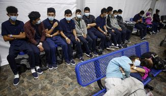 In this March 30, 2021, file photo, young unaccompanied migrants wait for their turn at the secondary processing station inside the U.S. Customs and Border Protection facility, the main detention center for unaccompanied children in the Rio Grande Valley, in Donna, Texas. U.S. authorities say they picked up nearly 19,000 children traveling alone across the Mexican border in March. It's the largest monthly number ever recorded and a major test for President Joe Biden as he reverses many of his predecessor's hardline immigration tactics. (AP Photo/Dario Lopez-Mills, Pool, File)