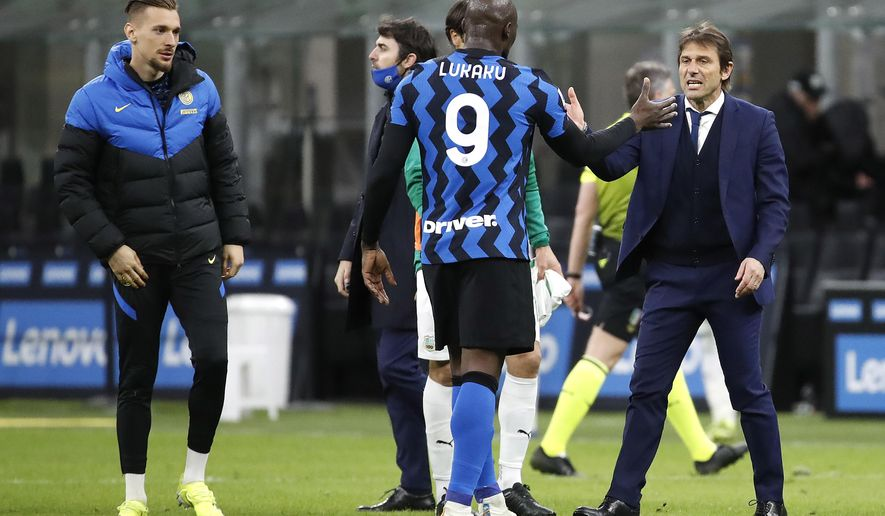 Inter Milan's head coach Antonio Conte with his player Romelu Lukaku, center, after the end of the Serie A soccer match between Inter Milan and Sassuolo at the San Siro Stadium in Milan, Italy, Wednesday, April 7, 2021. Inter Milan win the game 2-1. (AP Photo/Antonio Calanni)