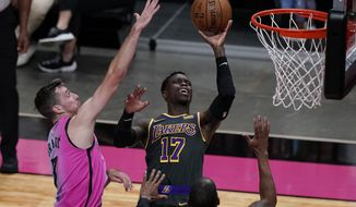 Los Angeles Lakers guard Dennis Schroder (17) drives to the basket as Miami Heat guard Goran Dragic (7) defends, during the first half of an NBA basketball game, Thursday, April 8, 2021, in Miami. (AP Photo/Marta Lavandier)