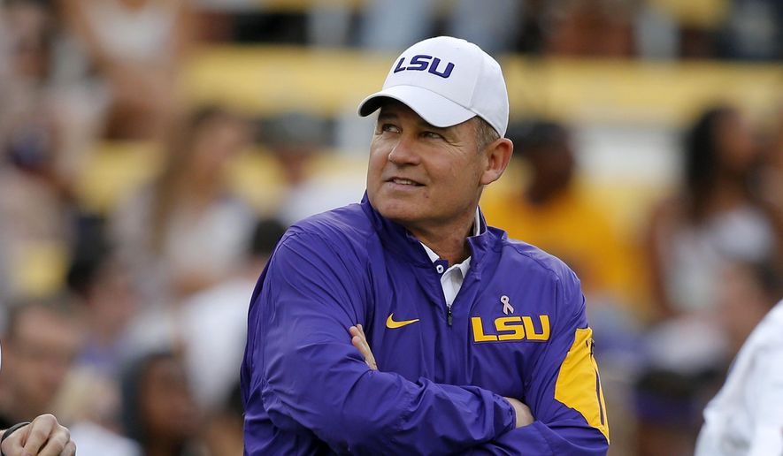 Then-LSU head coach Les Miles watches his team warm up before an NCAA college football game against Florida in Baton Rouge, La., in this Saturday, Oct. 17, 2015, file photo. In a $50 million federal racketeering lawsuit, an associate athletic director at LSU accuses university officials of retaliating against her for reporting racist remarks and inappropriate sexual behavior by former head football coach Les Miles. (AP Photo/Gerald Herbert, File) **FILE**