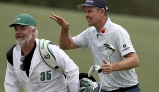 Justin Rose and his caddie David Clark react to his second shot on the eighteenth hole during the first round of the Masters golf tournament at Augusta National Golf Club, Thursday, April 8, 2021, in Augusta, Ga. (Curtis Compton/Atlanta Journal-Constitution via AP)