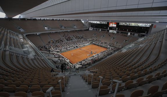 In this file photo dated Sunday, Oct. 11, 2020, rows of empty seats are seen at centre court at the Roland Garros stadium in Paris as Serbia's Novak Djokovic and Spain's Rafael Nadal warm up for the final match of the French Open tennis tournament.  The 2021 French Open schedule is being disrupted by the coronavirus pandemic for the second year in a row, as organizers said Thursday April 8, 2021, the Grand Slam tournament will be delayed by one week because of surging virus cases in France.(AP Photo/Alessandra Tarantino, FILE) **FILE**