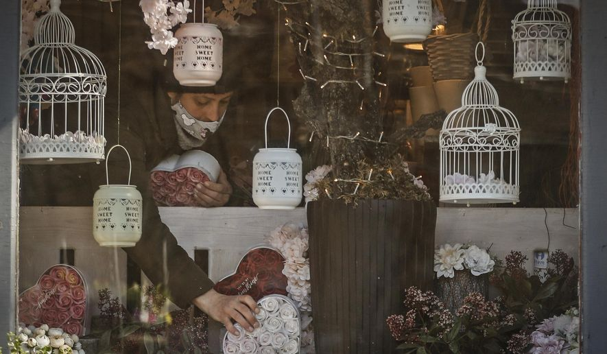 A staff member of a flower shop sets up merchandise in the window in Budapest, Hungary, Wednesday April 7, 2021. Hungary's government lifted several lockdown restrictions on Wednesday, even as some doctors and medical experts urged caution after a record-breaking day of COVID-19 deaths, a move that came as Hungary reached 2.5 million first-dose vaccinations, a benchmark the government set for when a gradual reopening could move forward. (AP Photo/Laszlo Balogh)