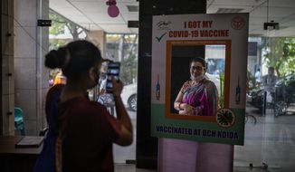 A woman poses for a photograph behind a cutout after receiving a COVID- 19 vaccine at a government hospital in Noida, a suburb of New Delhi, India, Wednesday, April 7, 2021. India hits another new peak with 115,736 coronavirus cases reported in the past 24 hours with New Delhi, Mumbai and dozens of other cities imposing night curfews to check the soaring infections. (AP Photo/Altaf Qadri)