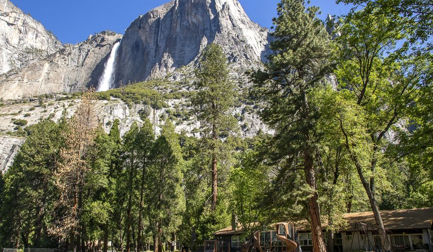 FILE - In this May 27, 2020, file photo provided by the National Park Service, Yosemite Valley School, lower right, stands in Yosemite National Park, Calif. In the background is Upper Yosemite Falls. Yosemite National Park will require advanced reservations for day visitors this summer, the park's peak tourist season, to limit the number of visitors and allow social distancing amid the coronavirus outbreak. Under the new rules, advance reservations will be required for day use visitors who enter Yosemite from May 21, 2021 to Sept. 30, 2021, the San Jose Mercury News reported. (Jamie Richards/National Park Service via AP, File)