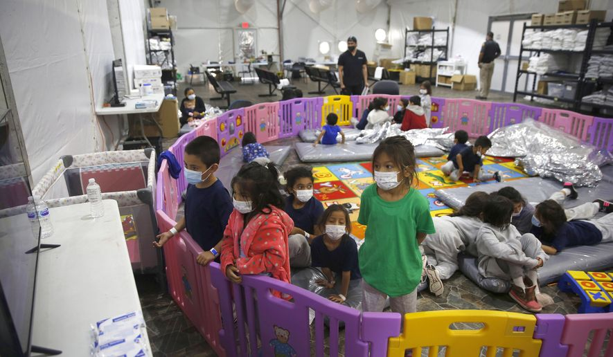 In this March 30, 2021, file photo, young unaccompanied migrants, from ages 3 to 9, watch television inside a playpen at the U.S. Customs and Border Protection facility, the main detention center for unaccompanied children in the Rio Grande Valley, in Donna, Texas. Migrant families will be held at hotels in the Phoenix area in response to a growing number of people crossing the U.S.-Mexico border, authorities said Friday, April 9, 2021, another step in the Biden administration's rush to set up temporary space for them (AP Photo/Dario Lopez-Mills, Pool, File)