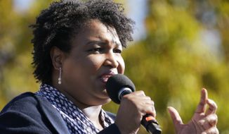 FILE - In this Nov. 2, 2020, file photo Stacey Abrams speaks to Biden supporters as they wait for former President Barack Obama to arrive and speak at a rally as he campaigns for Democratic presidential candidate former Vice President Joe Biden at Turner Field in Atlanta. In a new interview with The Associated Press, voting rights advocate Abrams discussed a new state law that tightens some Georgia voting rules after Democrats carried the state in the 2020 elections. (AP Photo/Brynn Anderson, File)
