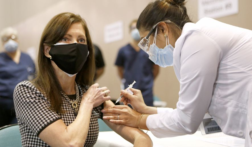 Neha Desai, a registered nurse with Atlantic Care, gives Tammy Murphy her first dose of COVID-19 vaccine at the Atlantic City Convention center, Friday, April 9, 2021 in Atlantic City, N.J.  (Tim Hawk /NJ Advance Media via AP)