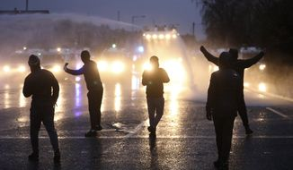 Nationalist youths gesture toward a police line blocking a road near the Peace Wall in West Belfast, Northern Ireland, Thursday, April 8, 2021. (AP Photo/Peter Morrison)