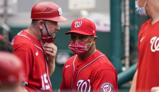 Washington Nationals manager Dave Martinez, center, walks in the dugout during the sixth inning of the second baseball game of the team's doubleheader against the Atlanta Braves at Nationals Park, Wednesday, April 7, 2021, in Washington. The Braves won 2-0. (AP Photo/Alex Brandon) **FILE**