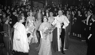FILE - In this March 28, 1939 file photo, Britain's Queen Elizabeth with the Lord Mayor of London passes through the Council Chamber of the Guildhall to attend a party and reception in aid of the National Birthday Trust Fund in the Guildhall, London, after receiving purses from debutantes and peeresses. Prince Philip was the longest serving royal consort in British history. In Britain, the husband or wife of the monarch is known as consort, a position that carries immense prestige but has no constitutional role. The wife of King George VI, who outlived him by 50 years, was loved as the Queen Mother. (AP Photo/Leslie Priest, File)