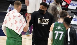 Dallas Mavericks' Kristaps Porzingis, left, and Luka Doncic (77) greet Milwaukee Bucks' Giannis Antetokounmpo, center, after their NBA basketball game in Dallas, Thursday, April 8, 2021. Antetokounmpo did not play in the 116-101 loss to the Mavericks. (AP Photo/Tony Gutierrez)