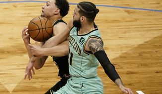 Milwaukee Bucks' Bryn Forbes and Charlotte Hornets' Cody Martin go after a loose ball during the first half of an NBA basketball game Friday, April 9, 2021, in Milwaukee. (AP Photo/Morry Gash)
