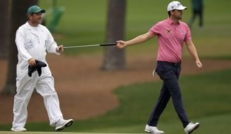 Bernd Wiesberger, of Austria, hands his putter to his caddie Jamie Lane after a birdie on the 15th hole during the second round of the Masters golf tournament on Friday, April 9, 2021, in Augusta, Ga. (AP Photo/David J. Phillip)
