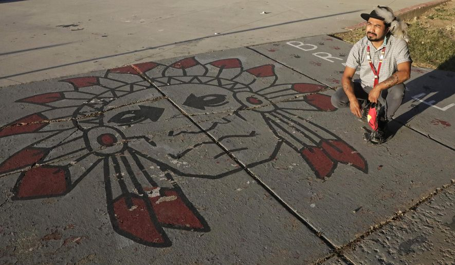 FILE - In this July 28, 2020, file photo, Native American advocate Carl Moore sits next to Native American imagery painted along a walkway which leads from the Bountiful High School parking lot up to the football field in Bountiful, Utah. A primarily white high school near Salt Lake City began replacing its hotly-contested Braves mascot after nearly 70 years. Principal Aaron Hogge announced on Friday, April 9, 2021, that the Redhawks would become Bountiful High School's mascot starting next fall. The school's new logo will be released sometime between now and the new school year. (AP Photo/Rick Bowmer, File)