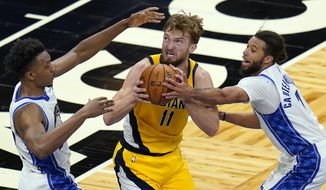 Indiana Pacers forward Domantas Sabonis (11) looks for a shot as he is defended by Orlando Magic center Wendell Carter Jr., left, and guard Michael Carter-Williams, right, during the second half of an NBA basketball game, Friday, April 9, 2021, in Orlando, Fla. (AP Photo/John Raoux)