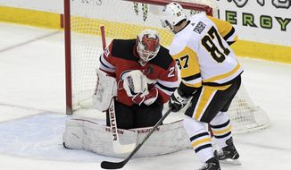 New Jersey Devils goaltender Mackenzie Blackwood (29) stops a shot by Pittsburgh Penguins center Sidney Crosby (87) during the first period of an NHL hockey game Friday, April 9, 2021, in Newark, N.J. (AP Photo/Bill Kostroun)