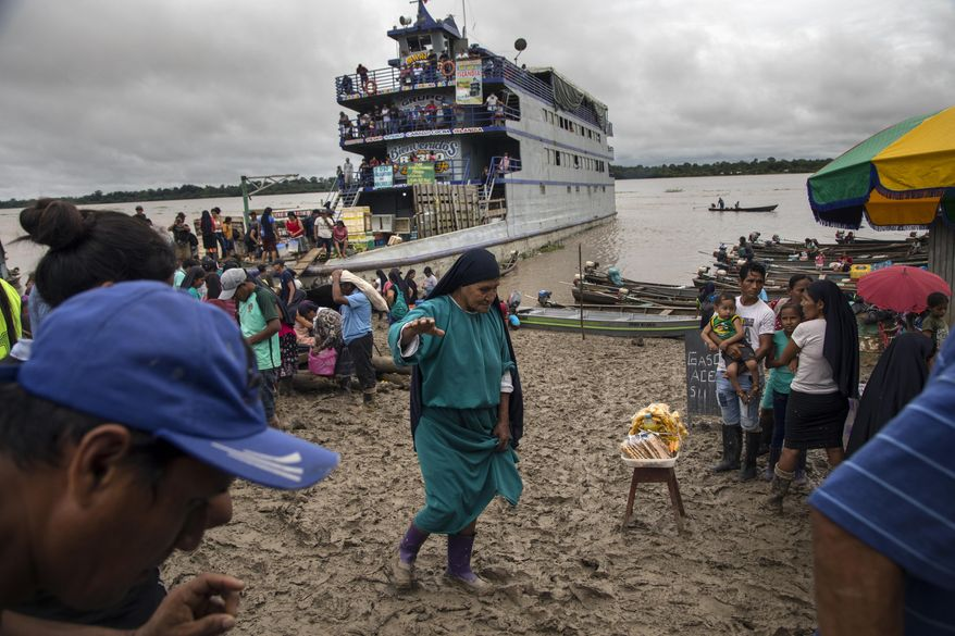A member of the Israelites of the New Universal Pact religious group, holds out her right arm to maintain her balance as she walks through a market on the muddy banks of the Amazon River, in Alto Monte de Israel, Peru, Sunday, March 28, 2021. The political arm of the messianic group, the Agricultural People's Front of Peru, known as Frepap, has emerged as a potential favorite in Sunday's April 11th legislative elections. (AP Photo/Rodrigo Abd)