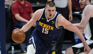 Denver Nuggets center Nikola Jokic, left, drives past San Antonio Spurs center Jakob Poeltl in the second half of an NBA basketball game Friday, April 9, 2021, in Denver. (AP Photo/David Zalubowski)