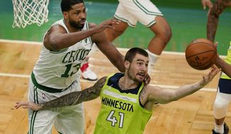 Minnesota Timberwolves forward Juancho Hernangomez (41) grabs a rebound in front of Boston Celtics center Tristan Thompson (13) in the first quarter of an NBA basketball game, Friday, April 9, 2021, in Boston. (AP Photo/Elise Amendola)