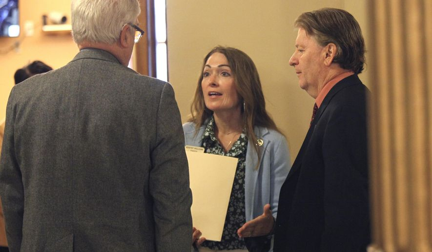 """Kansas state Reps. Jerry Stogsdill, left, D-Prairie Village, Kristey Williams, center, R-Augusta, and Steve Huebert, right, R-Valley Center, confer in a hallway during a break in negotiations with the Senate over education policy at the Statehouse, Thursday, April 8, 2021, in Topeka, Kan. Williams and Huebert agreed with senators to push forward a proposed ban on transgender athletes in girls' and women's school sports, but Stogsdill has called the measure """"morally wrong."""" (AP Photo/John Hanna)"""