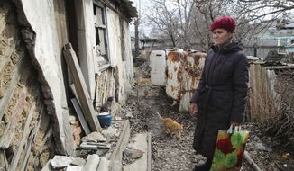 A woman visits her home in the separatist-controlled territory to collect her belongings after a recent shelling near a frontline outside Donetsk, eastern Ukraine, Friday, April 9, 2021. Tensions have built up in recent weeks in the area of the separatist conflict in eastern Ukraine, with violations of a cease-fire becoming increasingly frequent. (AP Photo)