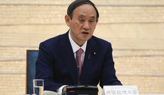 Japanese Prime Minister Yoshihide Suga announces that Tokyo, Kyoto and Okinawa will be applied for pre-emergency status under a new prevention law during a government task force meeting at the prime minister's office Friday, April 9, 2021, in Tokyo. Japan announced Friday that it will raise the coronavirus alert level in Tokyo to allow tougher measures to curb the rapid spread of a more contagious variant ahead of the Summer Olympics. (AP Photo/Eugene Hoshiko, Pool)