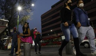 Transgender sex worker Geraldine wearing cat make-up, sits on her usual corner as she waits for clients outside the Revolution subway station, in Mexico City, Saturday, March 13, 2021. Geraldine, 30, a sex worker since age 15, says many of her regular clients have stopped coming amid the coronavirus pandemic and that seeing new clients presents new health and security risks. She is most concerned about the risk of bringing COVID-19 home to her partner, who has diabetes. (AP Photo/Rebecca Blackwell)