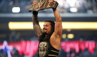 FILE - In this April 3, 2016, file photo, Roman Reigns holds up the championship belt after defeating Triple H during WrestleMania 32 at AT&T Stadium in Arlington, Texas.  WWE is set to welcome back fans for the first time in more than a year when 25,000 fans are expected on both Saturday, April 10, 2021 and Sunday nights for WrestleMania at Raymond James Stadium in Tampa, Fla.   (Jae S. Lee/The Dallas Morning News via AP, File)
