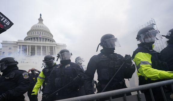 In this Jan. 6, 2021, file photo, police stand guard after holding off violent rioters who tried to break through a police barrier at the Capitol in Washington. (AP Photo/Julio Cortez, File)  **FILE**