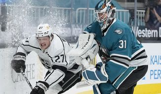 Los Angeles Kings left wing Austin Wagner (27) collides with San Jose Sharks goaltender Martin Jones (31) during the second period of an NHL hockey game Friday, April 9, 2021, in San Jose, Calif. (AP Photo/Tony Avelar)