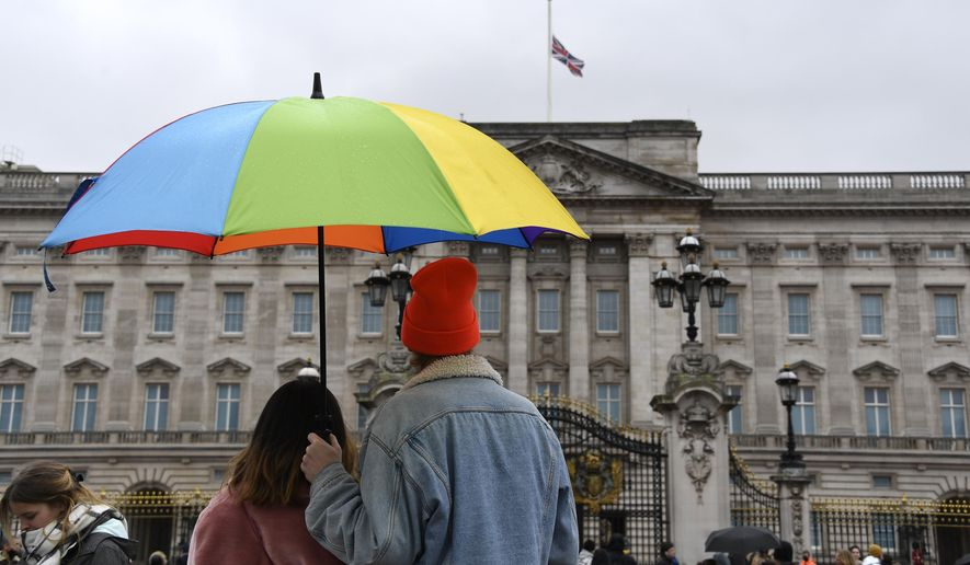 A couple under an umbrella look at the Union flag at half-staff over Buckingham Palace in London, a day after the death of Britain's Prince Philip, Saturday, April 10, 2021. Britain's Prince Philip, the irascible and tough-minded husband of Queen Elizabeth II who spent more than seven decades supporting his wife in a role that mostly defined his life, died on Friday. (AP Photo/Alberto Pezzali)