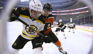 Boston Bruins' Jeremy Lauzon, left, and Philadelphia Flyers' Joel Farabee battle along the boards for the puck during the first period of an NHL hockey game, Saturday, April 10, 2021, in Philadelphia. (AP Photo/Derik Hamilton)