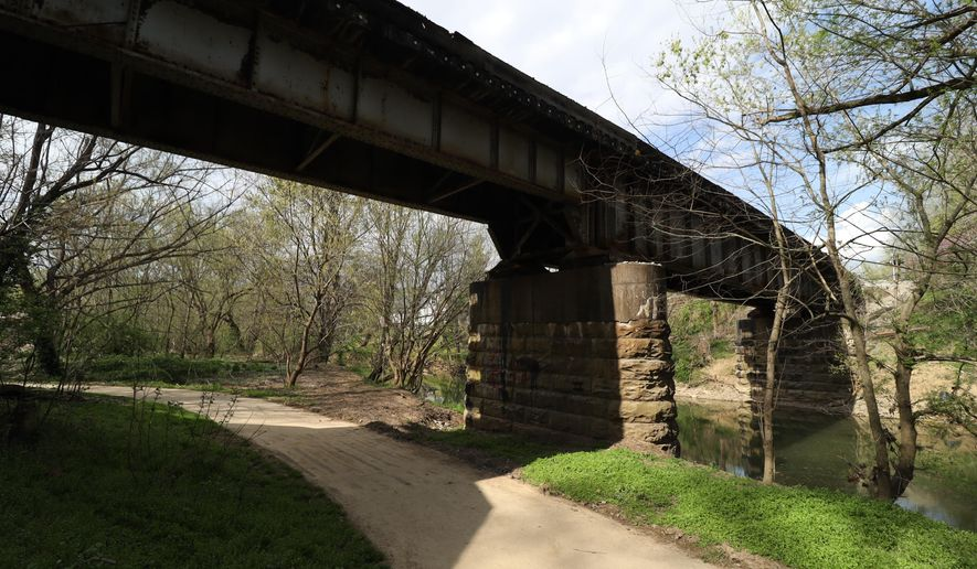 A train trestle bridge crosses over Clear Creek, Wednesday, April 7, 2021, in Shelbyville, Ky., where three black inmates were dragged out of the city's old jail and lynched in 1911. The city plans to unveil three markers outside of the old jail downtown to note the city's 6 lynchings from 1878 to 1911. (Marcus Dorsey/Lexington Herald-Leader via AP)