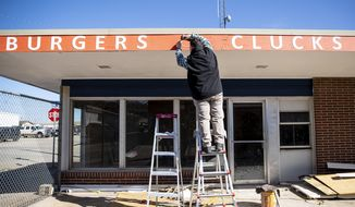 Aaron Cannon attaches signage to his new business, Ranch and Roost, a burger and fried chicken restaurant, Thursday, April 1, 2021, in downtown Gillette, Wyo. Cannon and his family were among a growing number of people real estate agents say are moving to Wyoming from elsewhere. (Mike Moore/Gillette News Record via AP)