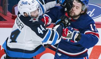 Montreal Canadiens' Josh Anderson (17) collides with Winnipeg Jets' Josh Morrissey during first-period NHL hockey game action in Montreal, Saturday, April 10, 2021. (Graham Hughes/The Canadian Press via AP)