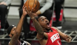 Houston Rockets forward Sterling Brown, right, shoots as Los Angeles Clippers forward Marcus Morris Sr. defends during the first half of an NBA basketball game Friday, April 9, 2021, in Los Angeles. (AP Photo/Mark J. Terrill)