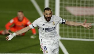 Real Madrid's Karim Benzema celebrates after scoring the opening goal during the Spanish La Liga soccer match between Real Madrid and FC Barcelona at the Alfredo di Stefano stadium in Madrid, Spain, Saturday, April 10, 2021. (AP Photo/Manu Fernandez)