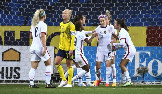 Megan Rapinoe (15) of USA celebrates with teammates after scoring a goal on a penalty kick during the women's international friendly soccer match between Sweden and USA at Friends Arena in Stockholm, Sweden, Saturday, April 10, 2021. (Janerik Henriksson/TT via AP)